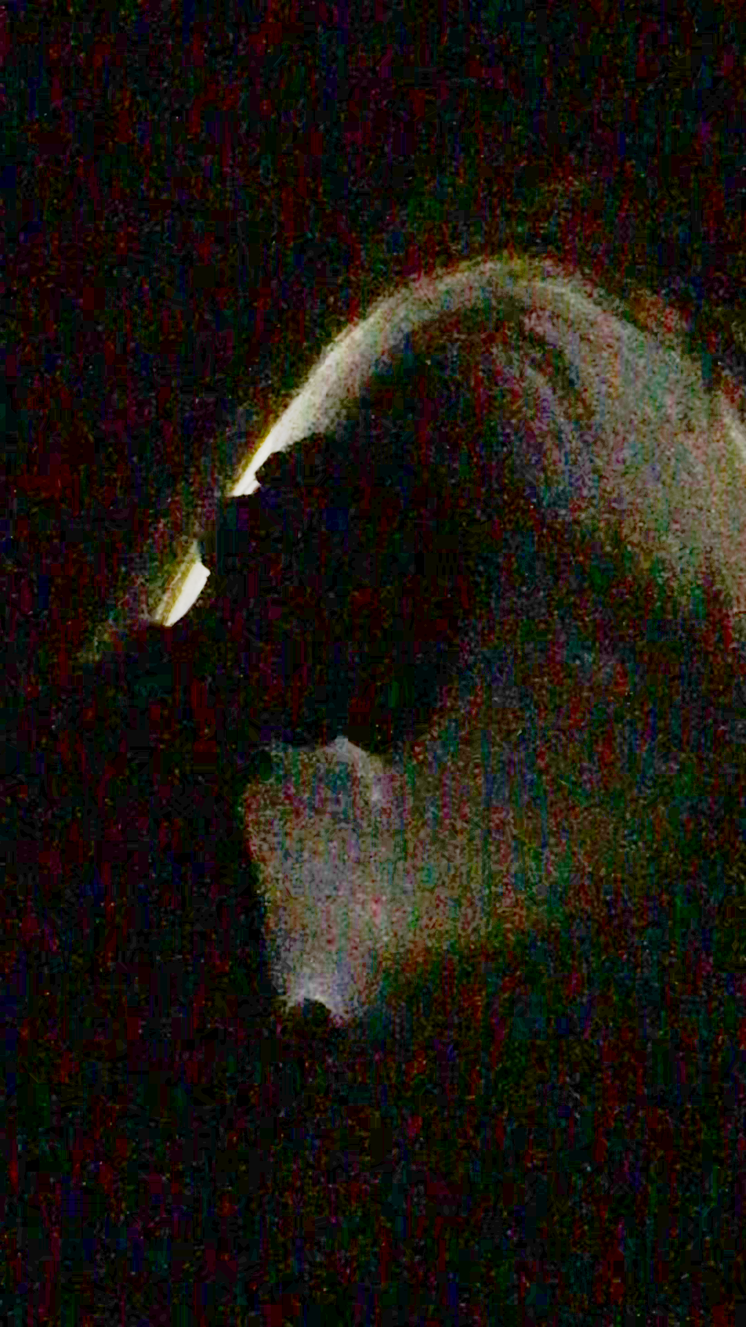 A low-fi photo of a person silhouette in a tunnel holding a light